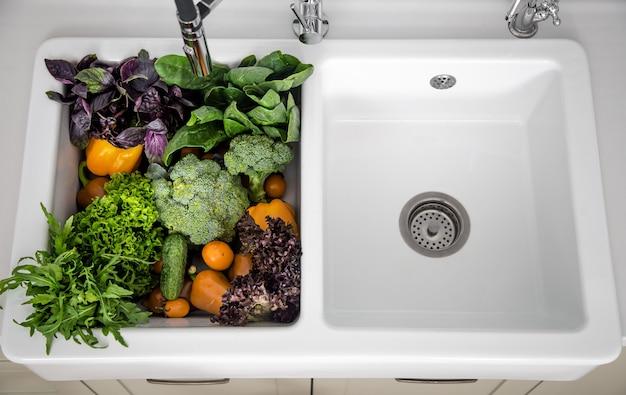 현대 부엌의 부엌 싱크대에 다양한 야채를 닫습니다.