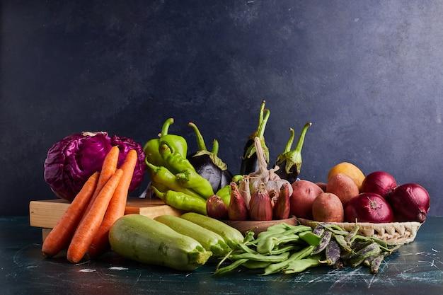 青いテーブルに分離されたさまざまな野菜。