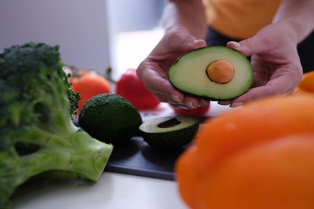 다양한 야채가 여자 손 클로즈업 테이블에 놓여 있습니다.