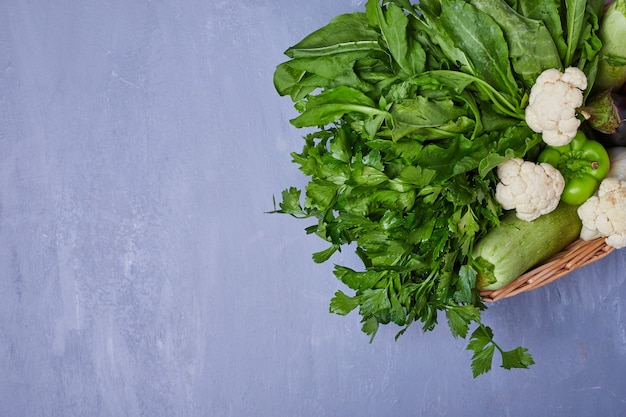 青の木板に野菜のバラエティ
