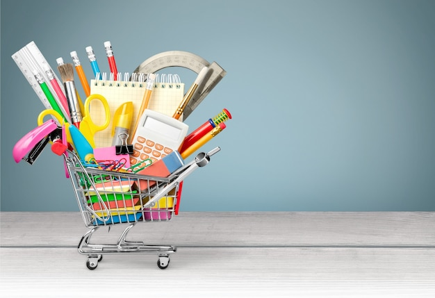 背景に緑のチョークボードと木製のテーブルの上の小さなショッピングカートの様々な事務用品