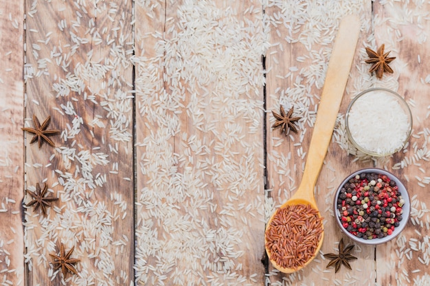 Variety of organic raw rice and tasty spices spread over wooden plank