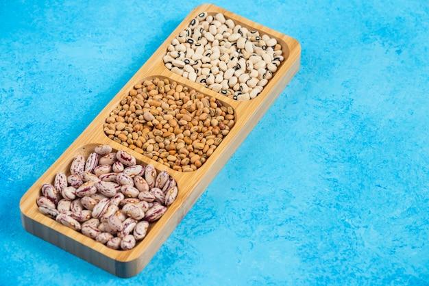 Varietà di fagioli crudi sul piatto di legno.