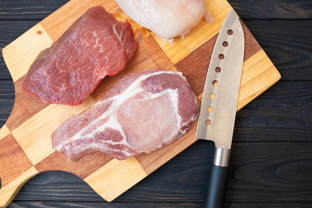 Variety of raw meat beef meat on bone, pork meat and chicken fillet on wooden table with butcher knife, top view