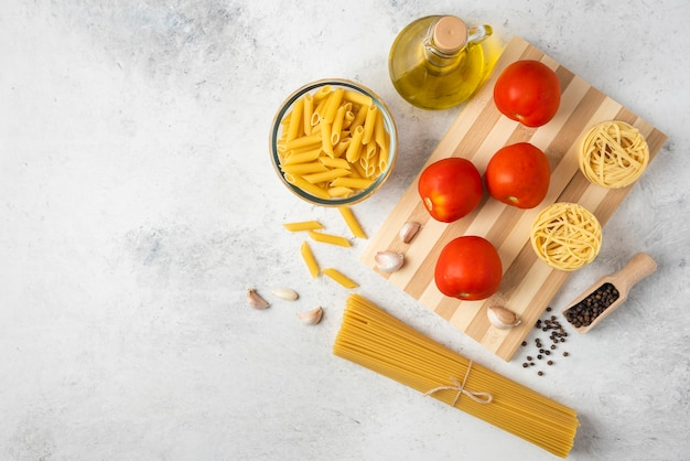 Variety of raw pasta, bottle of olive oil, pepper grains and tomatoes on white background.