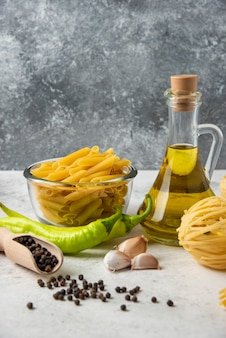 Variety of raw pasta, bottle of olive oil, pepper grains and vegetables on white table.