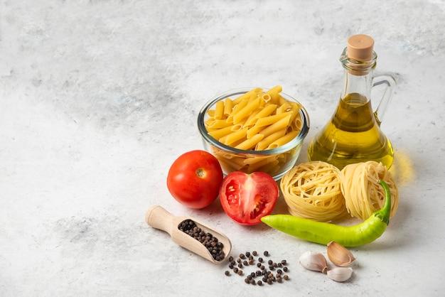 Varietà di pasta cruda, bottiglia di olio d'oliva, grani di pepe e verdure sul tavolo bianco.