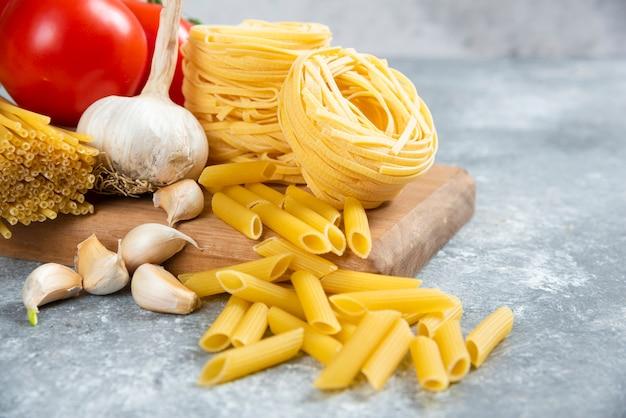 Varietà di pasta cruda, aglio e pomodori su tavola di legno.