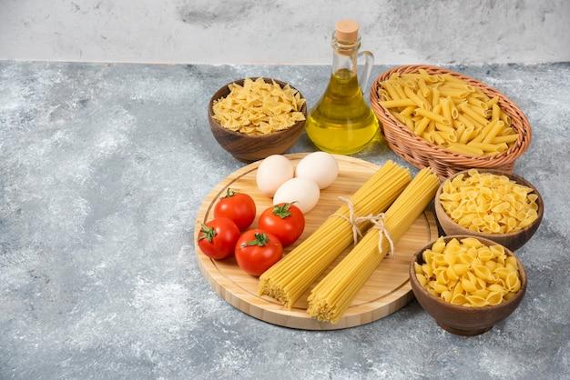 Varietà di pasta cruda con uova, pomodori freschi e bottiglia di olio sulla superficie in marmo.