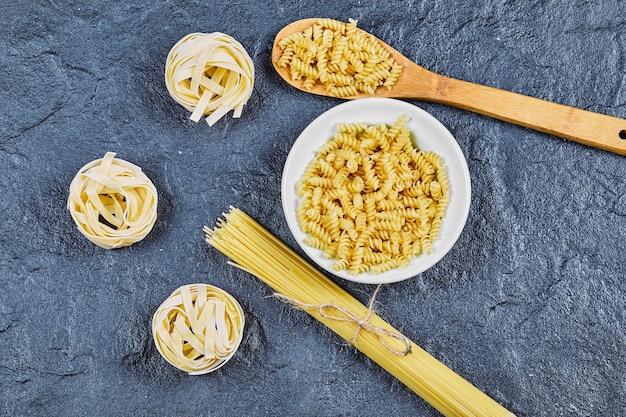 Varietà di pasta cruda con cucchiaio di legno su sfondo blu