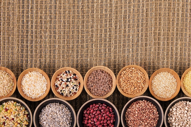 Variety of rice and grains in bowls on bamboo mat