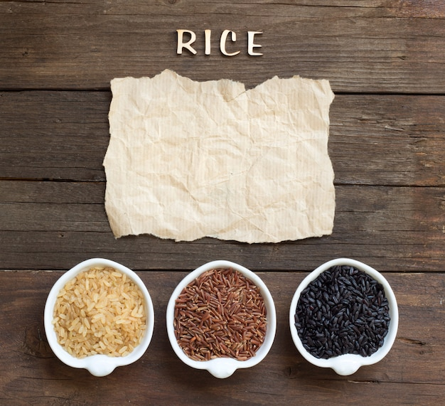 Variety of ricein bowls with craft paper and text rice made of wooden letters on a wooden background top view