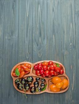 Разнообразие спелых натуральных органических вкусных помидоров. свежие сезонные местные овощи. группа свежих помидоров.