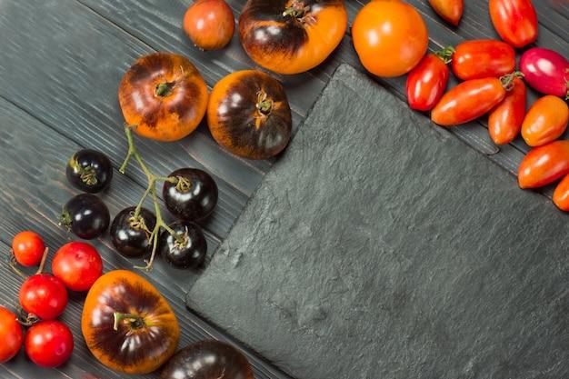 Разнообразие спелых натуральных органических вкусных помидоров. свежие сезонные местные овощи.