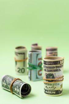 Variety of rolled currency on green background