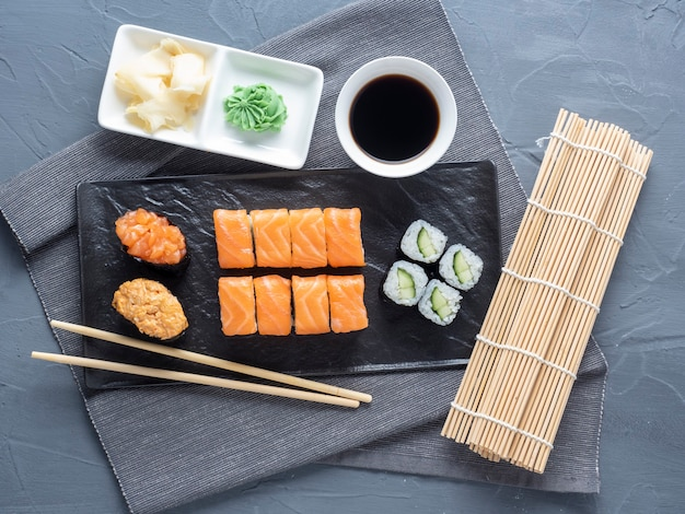 A variety of rolls and sushi gunkan nested on a black plate. next to it are bamboo wasabi sticks and sauce. top view, flat lay. traditional japanese cuisine