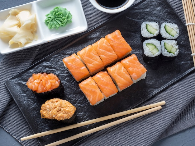 A variety of rolls and sushi gunkan nested on a black plate. next to it are bamboo wasabi sticks and sauce.