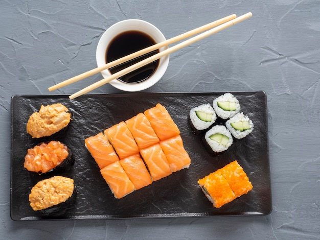 A variety of rolls and sushi gunkan nested on a black plate. next to it are bamboo wasabi sticks and sauce