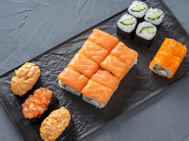 A variety of rolls and sushi gunkan nested on a black plate.