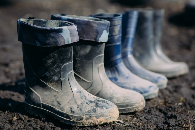 Variety of rubber boots in a line in the dirt in early spring