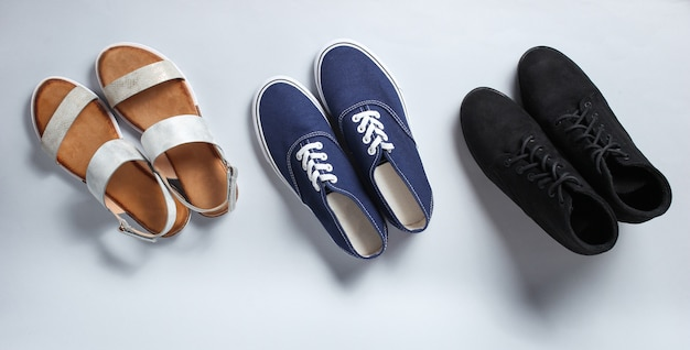 Variety of sandals, boots, sneakers on white.