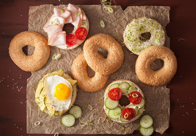 Variety of sandwiches on bagels with egg and vegetables