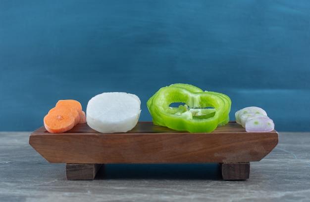 Una varietà di verdure affettate, sul tavolo di marmo.