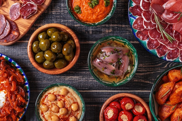 Variety slices jamon,  chorizo, salami, bowls with olives,  peppers, anchovies, spicy potatoes, mashed chickpeas on a wooden table.