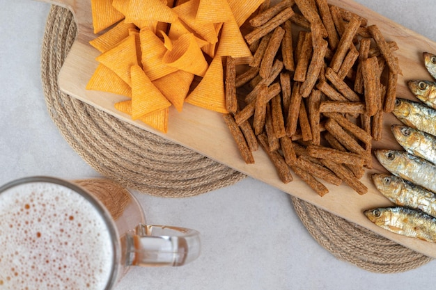Varietà di snack sulla tavola di legno con un bicchiere di birra.