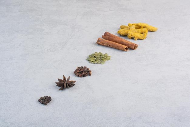 Varietà di spezie ed erbe aromatiche isolate su sfondo concreto.