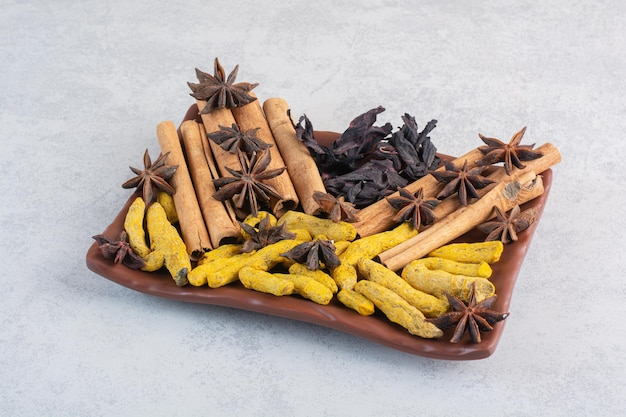 Variety of spices and herbs isolated on concrete surface.