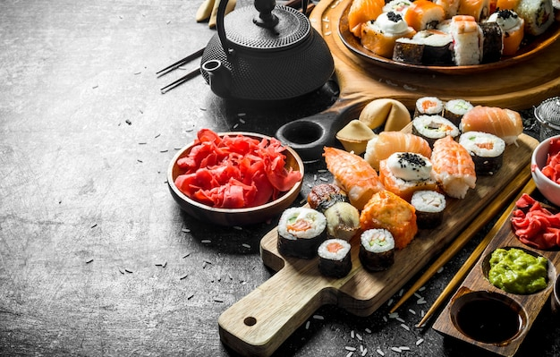 A variety of sushi, maki and rolls with ginger and soy sauce. on rustic surface
