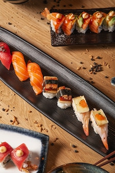 Variety of sushi and nigiri on the table served in ceramic plates.