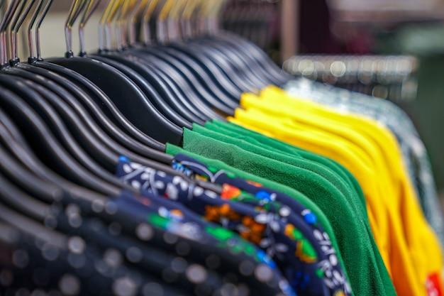 백화점 패션 천 매장 옷걸이에 다양한 스웨터 브랜드 이름이 걸려 있습니다.