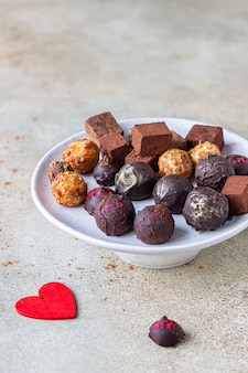 Variety of sweet homemade chocolate candies and truffles, light concrete surface.