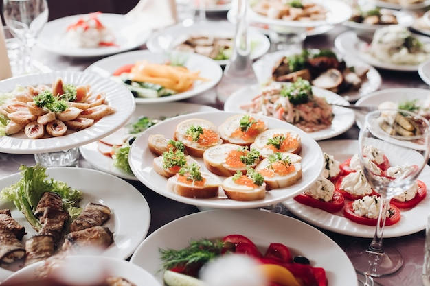 Variety of tasty cold snacks served on white ceramic plates over wedding banquet special occasion table. assortment of cooked snacks and food on table in restaurant. christmas or new year celebration.