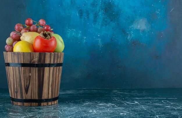 Varietà di gustosi frutti nel secchio di legno.