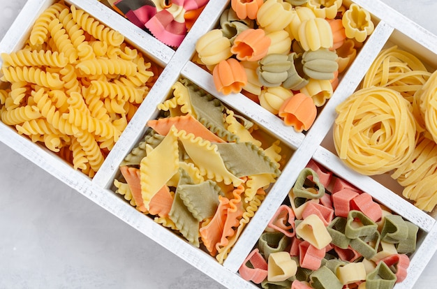 Variety of types and shapes of raw italian pasta. selective focus.