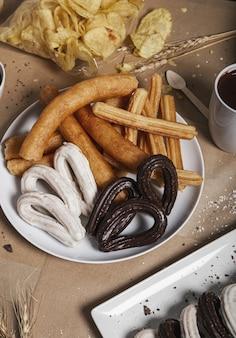 Varietà di churros tipici sono serviti al tavolo per la colazione.