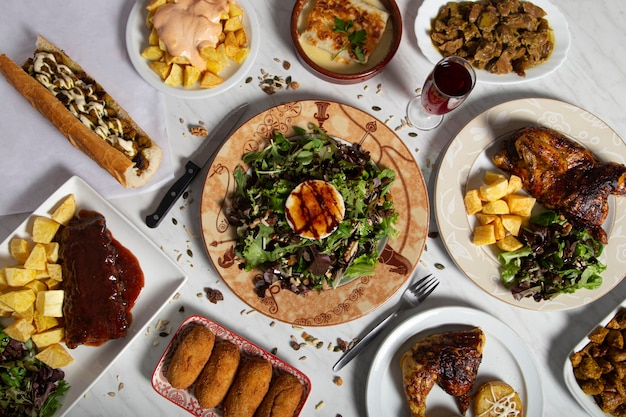 A variety of typical spanish dishes are served at the restaurant table. top view