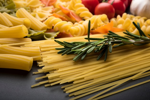 Variety of uncooked pasta on black background