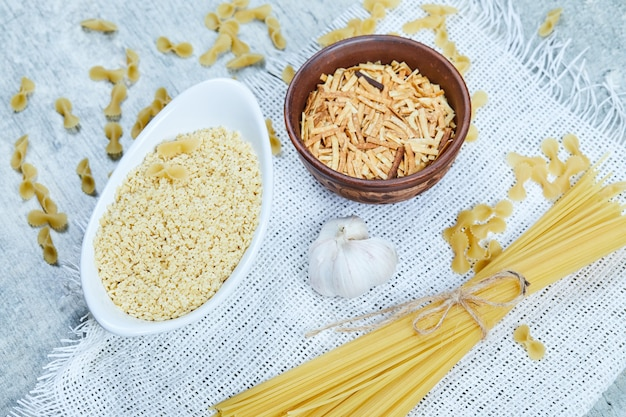 Variety of uncooked pasta with garlic and white tablecloth.