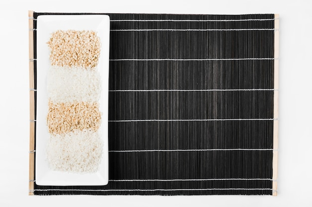 Varietà di riso crudo in vassoio bianco su placemat nero