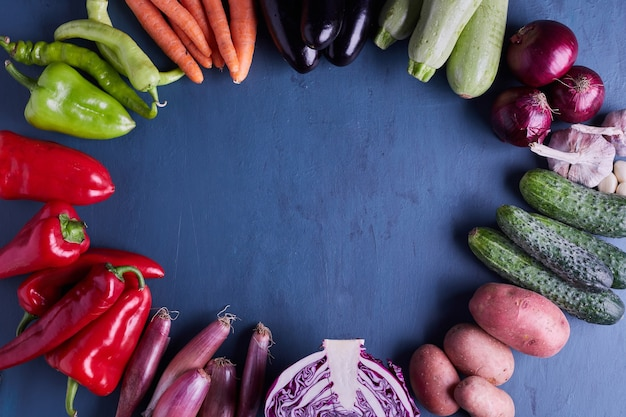 Variety of vegetables in a circle on blue table.
