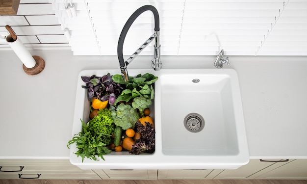 Variety of vegetables in the kitchen sink of modern kitchen close up.