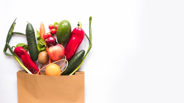 Variety of vegetables in paper bag over white background