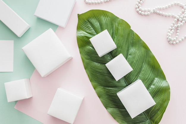 Variety of white boxes on pink and green paper background with green leaf