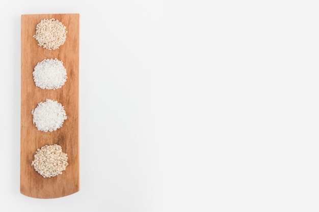 Variety of white and brown rice on wooden tray