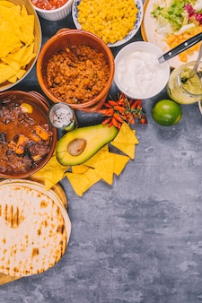 Variety of yummy mexican dishes over concrete background