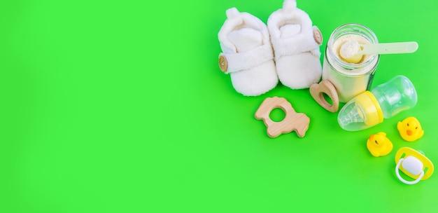 赤ちゃんのための様々なアクセサリー。緑の背景。セレクティブフォーカス。